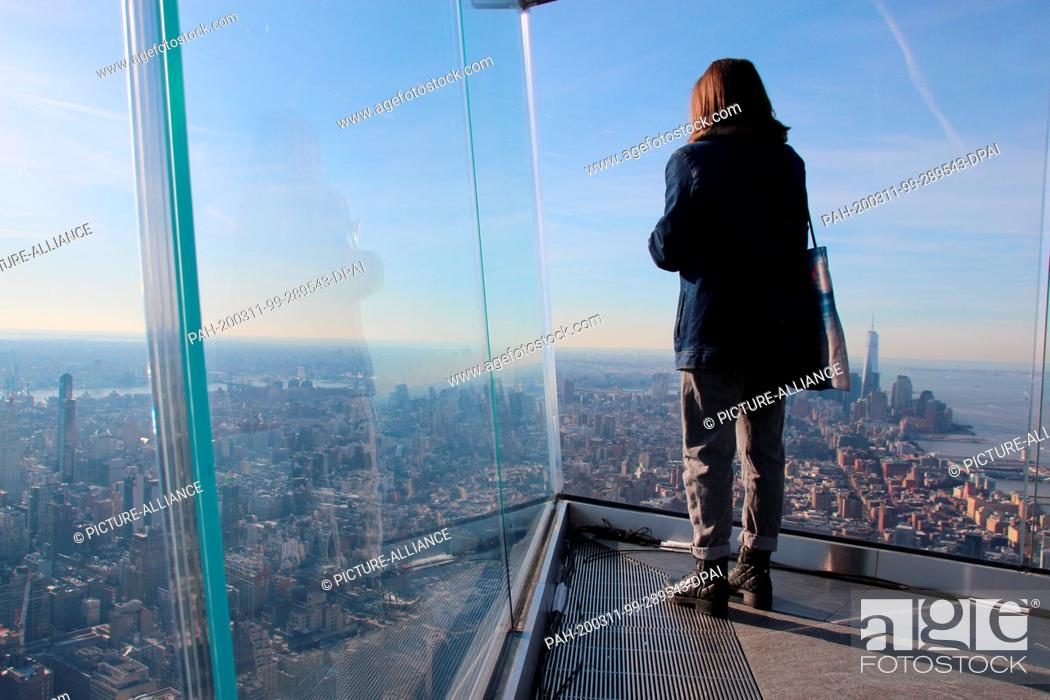 Stock Photo: 11 March 2020, US, New York: A woman is looking at the New York panorama from the new triangular viewing platform Edge. The platform is in one of the new.