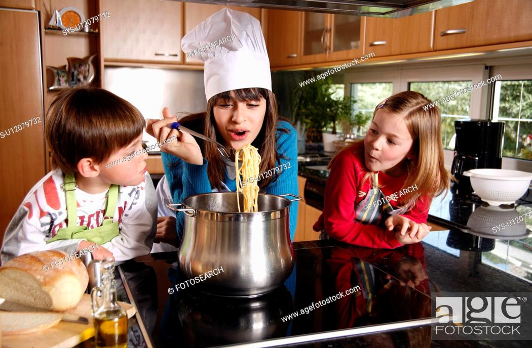 Stock Photo: Children cooking spaghetti.