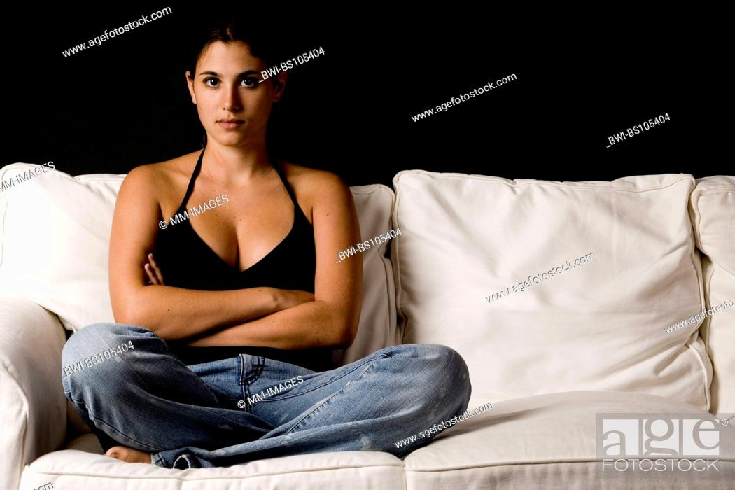 Stock Photo: A pretty young woman sits on a white sofa against a black background.