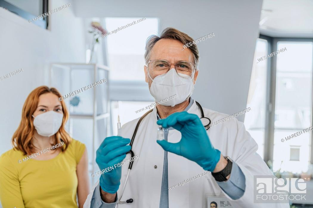 Stock Photo: Male doctor holding COVID-19 vaccination vial and syringe while standing with patient in background at examination room.