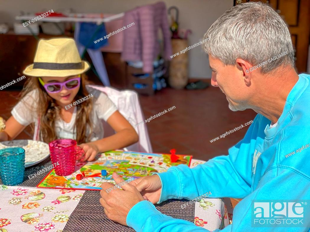 Stock Photo: Young girl playing goose game with her father outdoor.