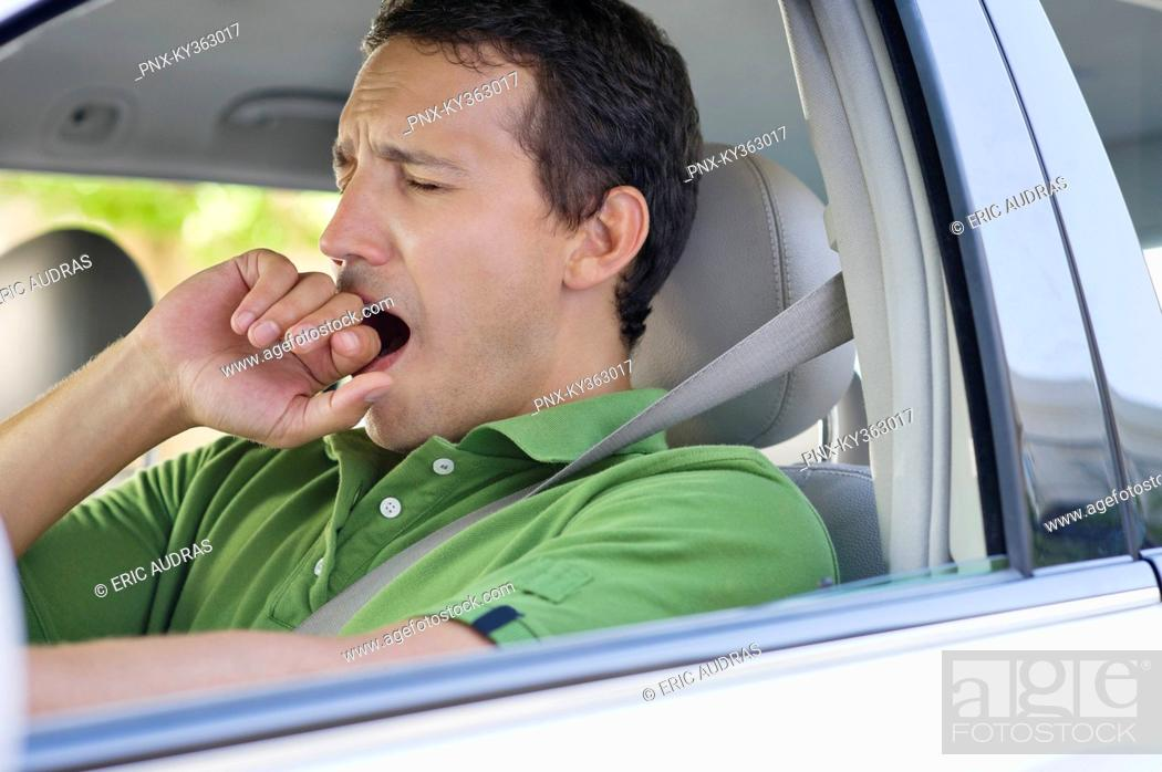 Stock Photo: Mid adult man yawning while driving a car.