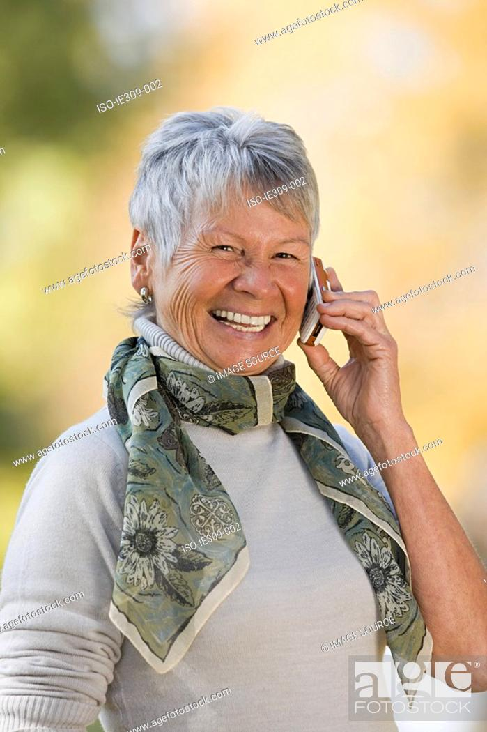 Stock Photo: Smiling senior woman using a cell phone.