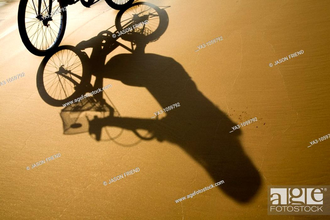 Stock Photo: Laos, Si Phan Don Four Thousand Islands, Don Khon  Female tourist on a hired bicycle on a sandy beach on the island of Don Knon.