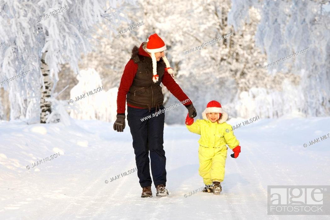 Stock Photo: Three years old girl with mother in snowy parkway.