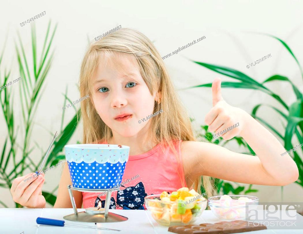 Stock Photo: Little girl preparing and eating a chocolate fondue. Chocolate fondue with kiwi, banana, apple, tangerine and marshmallow. Happy little girl.