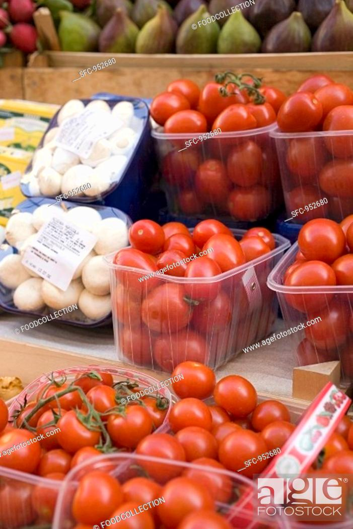 Stock Photo: Tomatoes and mushrooms in plastic punnets at a market.