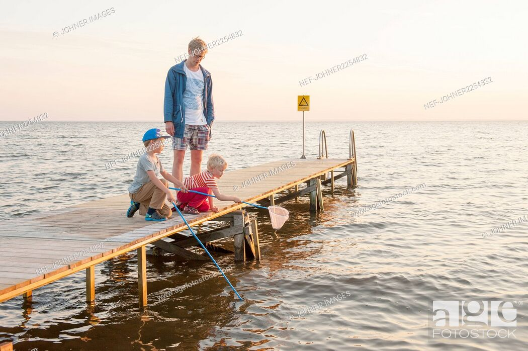 Stock Photo: Father with sons on jetty.