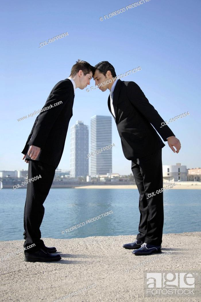 Stock Photo: Business men head to head by seafront.
