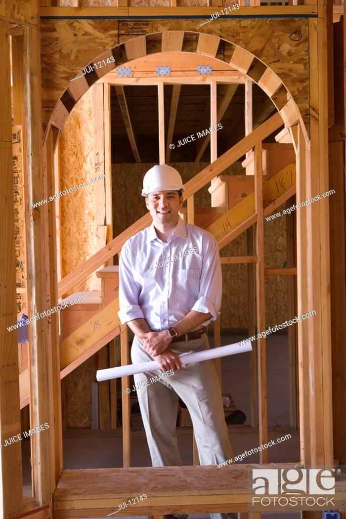 Stock Photo: Architect with blueprint in partially built house, smiling, portrait.