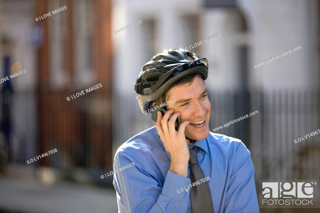 Stock Photo: A businessman on his bicycle, talking on his mobile phone.