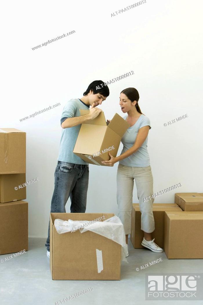Stock Photo: Couple unpacking, man showing contents of one box, woman's mouth open in surprise.
