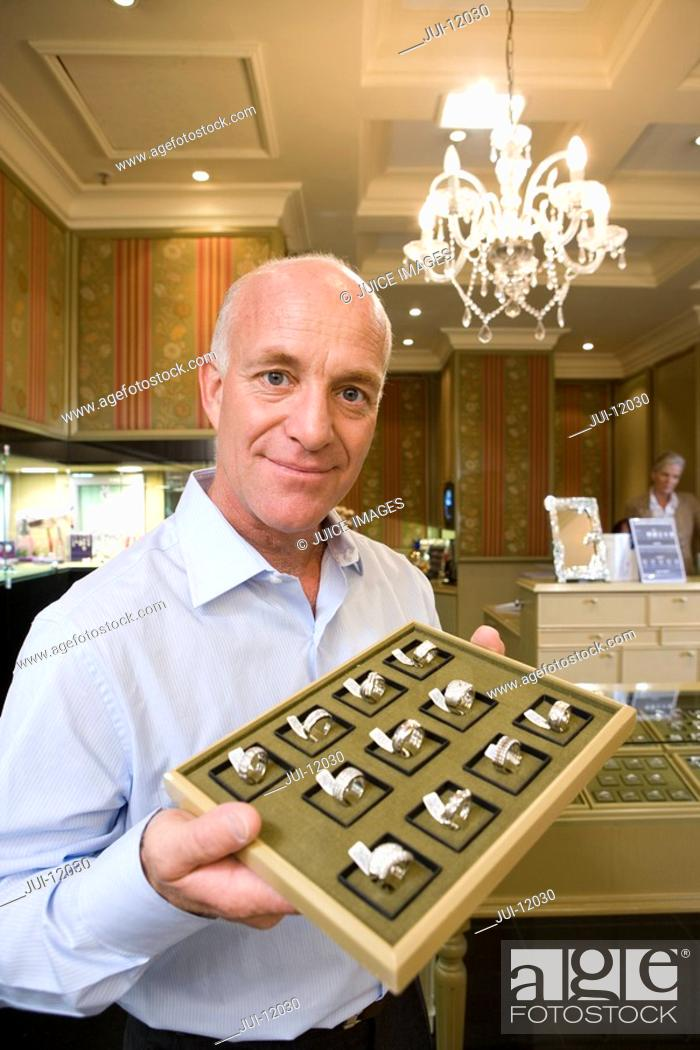 Stock Photo: Mature male jewellery shop assistant with tray of rings, smiling, portrait.