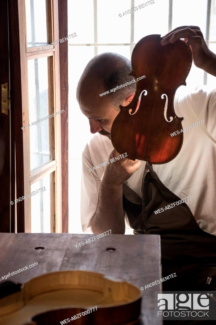 Imagen: Luthier tuning the top plate of a violin in his workshop.