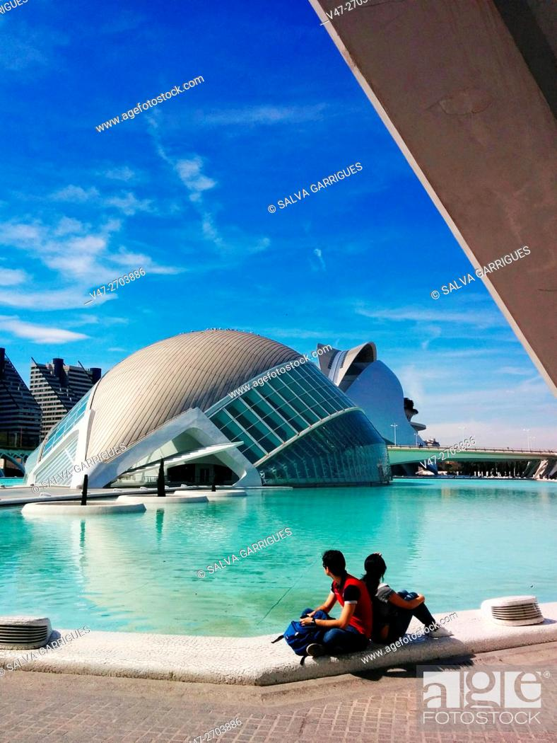 Imagen: Couple of tourists sitting on the lake and watching the Hemisferic, Valencia, Spain. Europe.