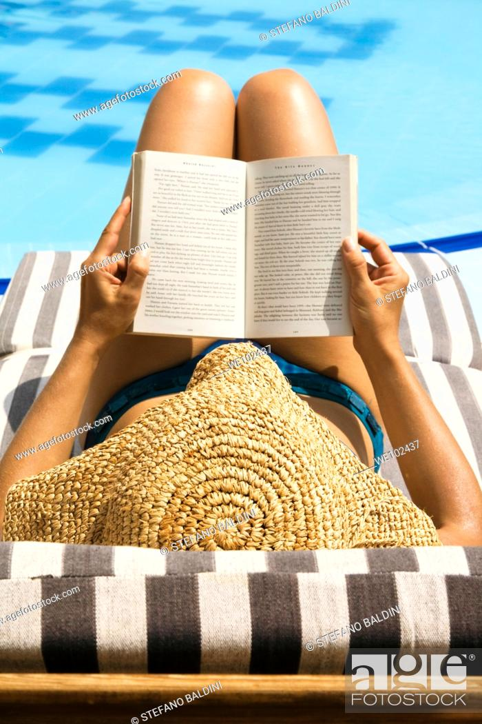 Stock Photo: Woman reading book by swimming pool.
