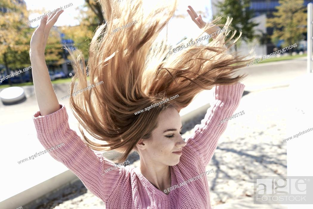 Stock Photo: Portrait of young woman with flying hair. Munich, Germany.