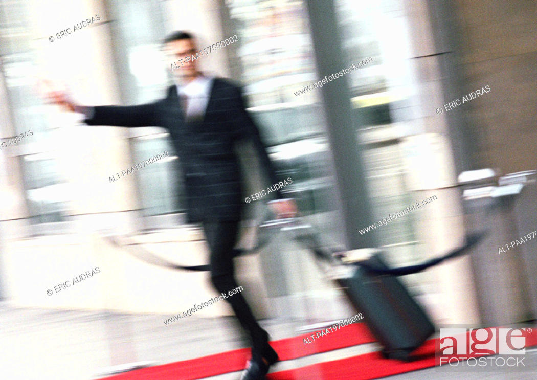 Stock Photo: Businessman with luggage, arm extended, blurred.