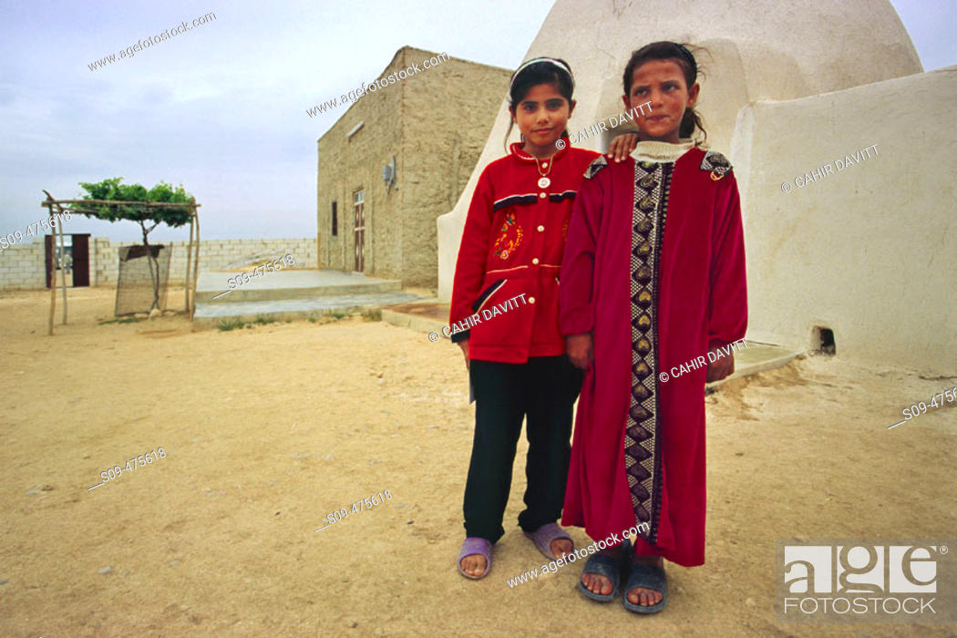 Stock Photo: Syrian Bedouin girls in local dress in a typical Beehive village near Aleppo, Halab, Syria.