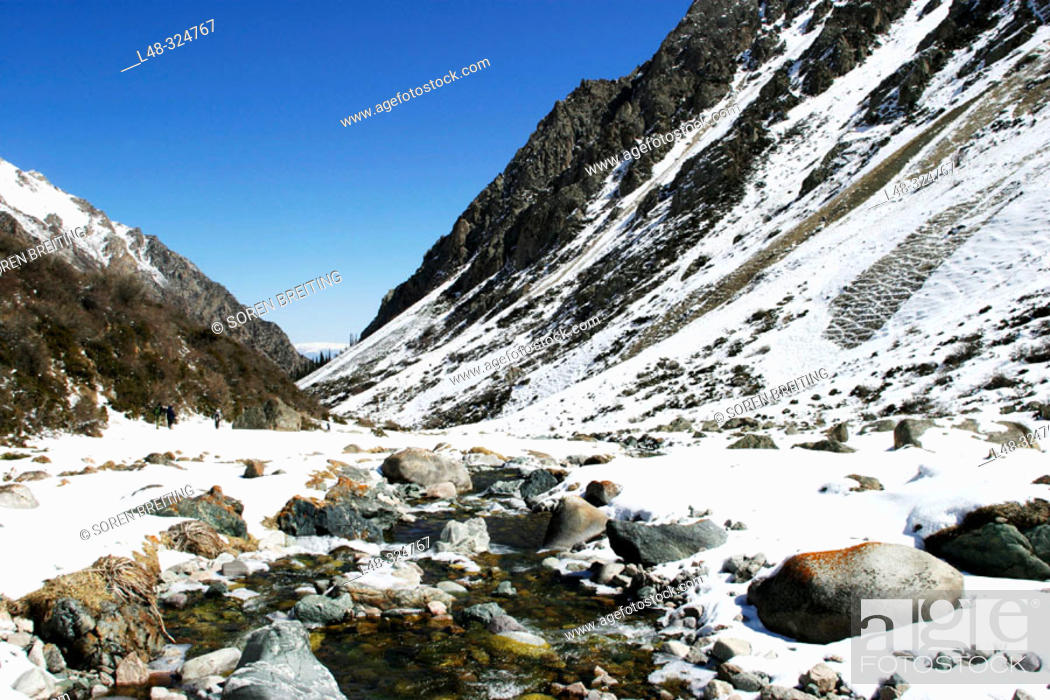 Stock Photo: Kyrgyzstan, Central Asia: Mountains and valley with stream and snow near the capital Bishkek during early spring in april. Trekkers in the distance.