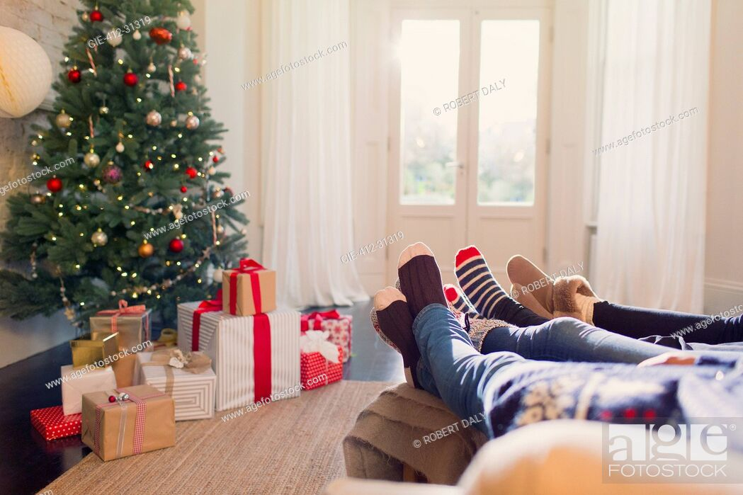 Stock Photo: Relaxed family in socks with feet up near Christmas tree.