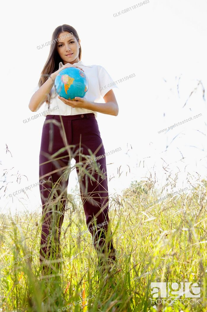 Stock Photo: Businesswoman holding a globe in a field.