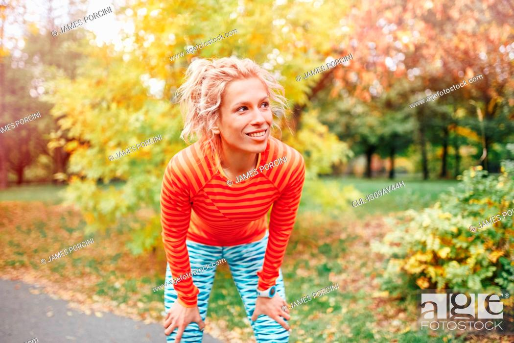 Stock Photo: Young female runner taking a break on park path.