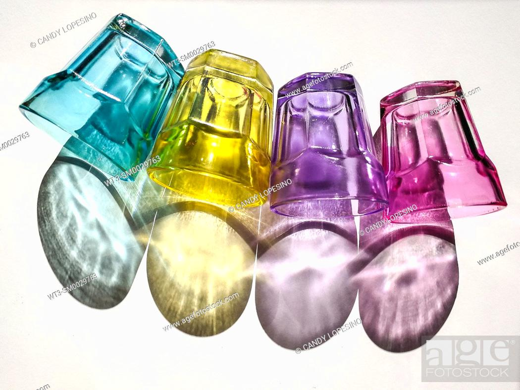Stock Photo: Four colored crystal glasses and their shadows on white background.