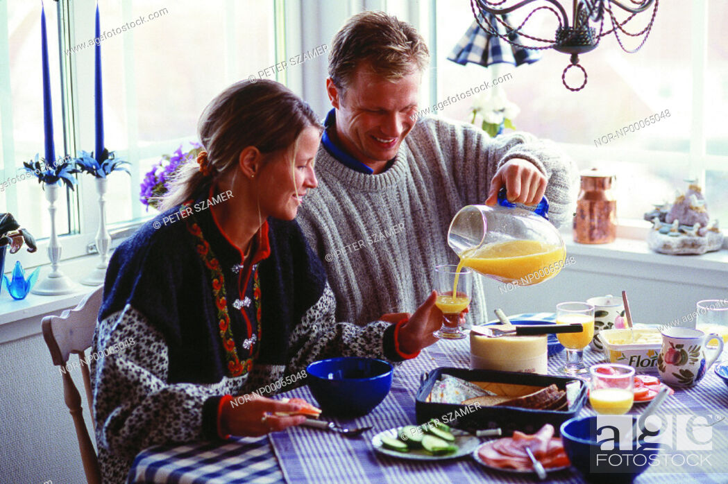 Stock Photo: A man pouring orangejuice into a glass for his wife at the breakfast table.