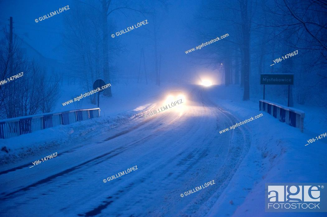 Stock Photo: Cars circulating at bight over a frozen road, Myslakowice, Poland.