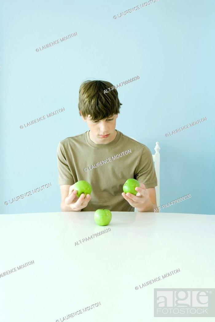 Stock Photo: Teen boy holding up comparing three apples.