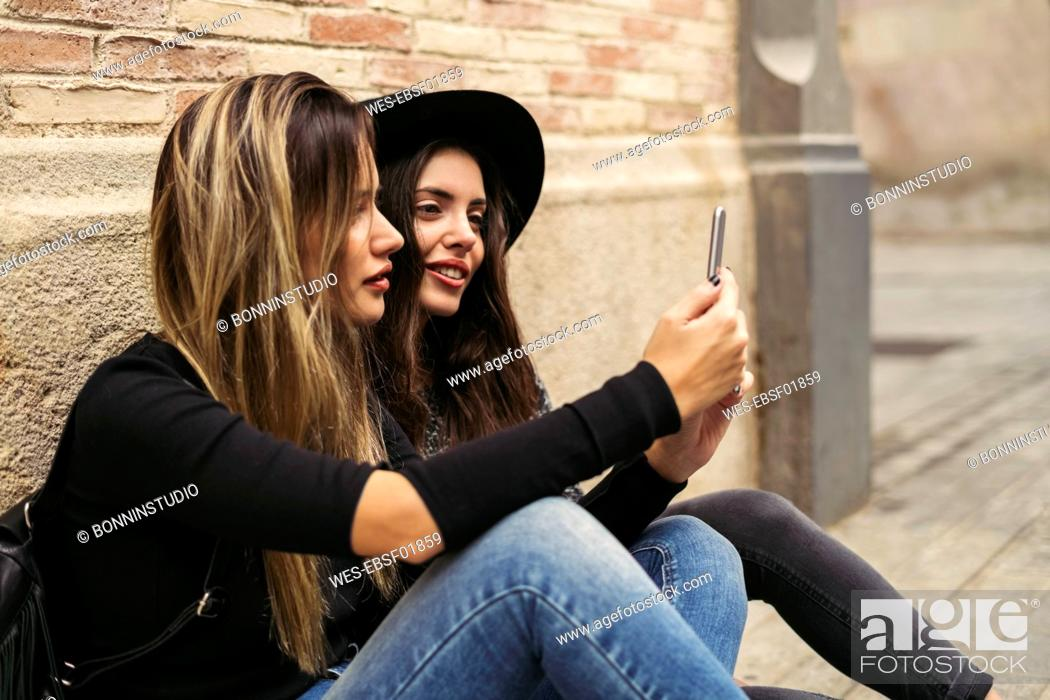 Stock Photo: Two best friends sitting on the ground looking at smartphone.