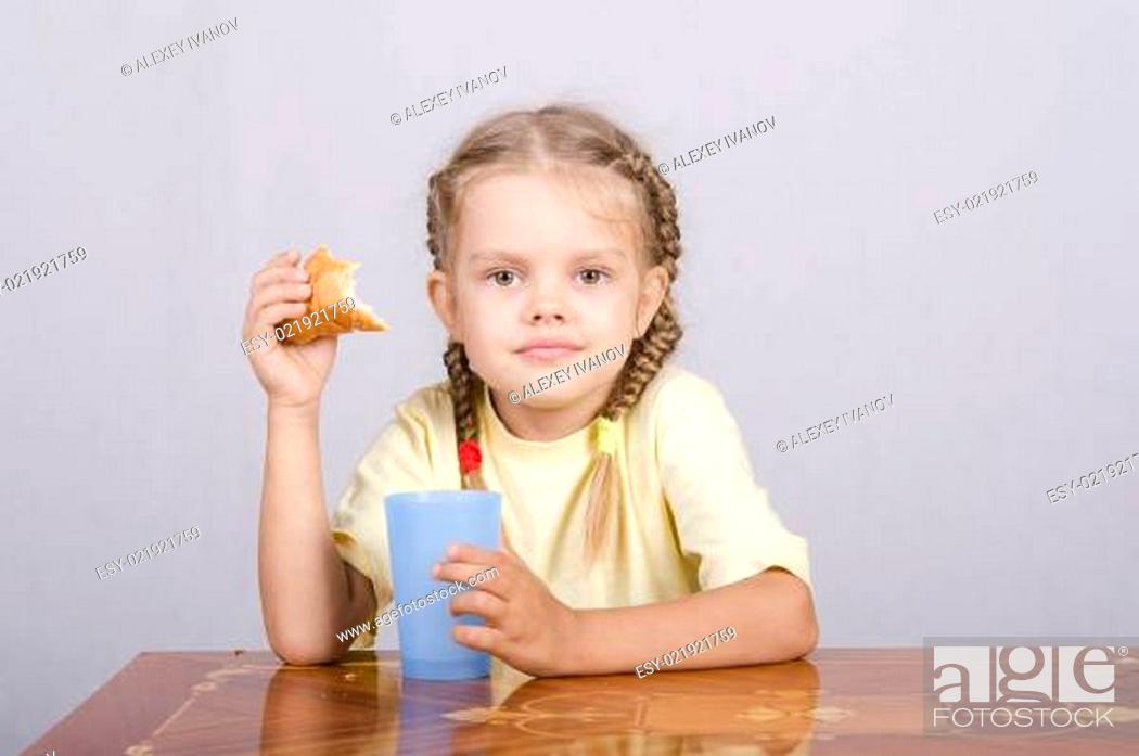 Stock Photo: Girl eating a muffin with juice at the table.