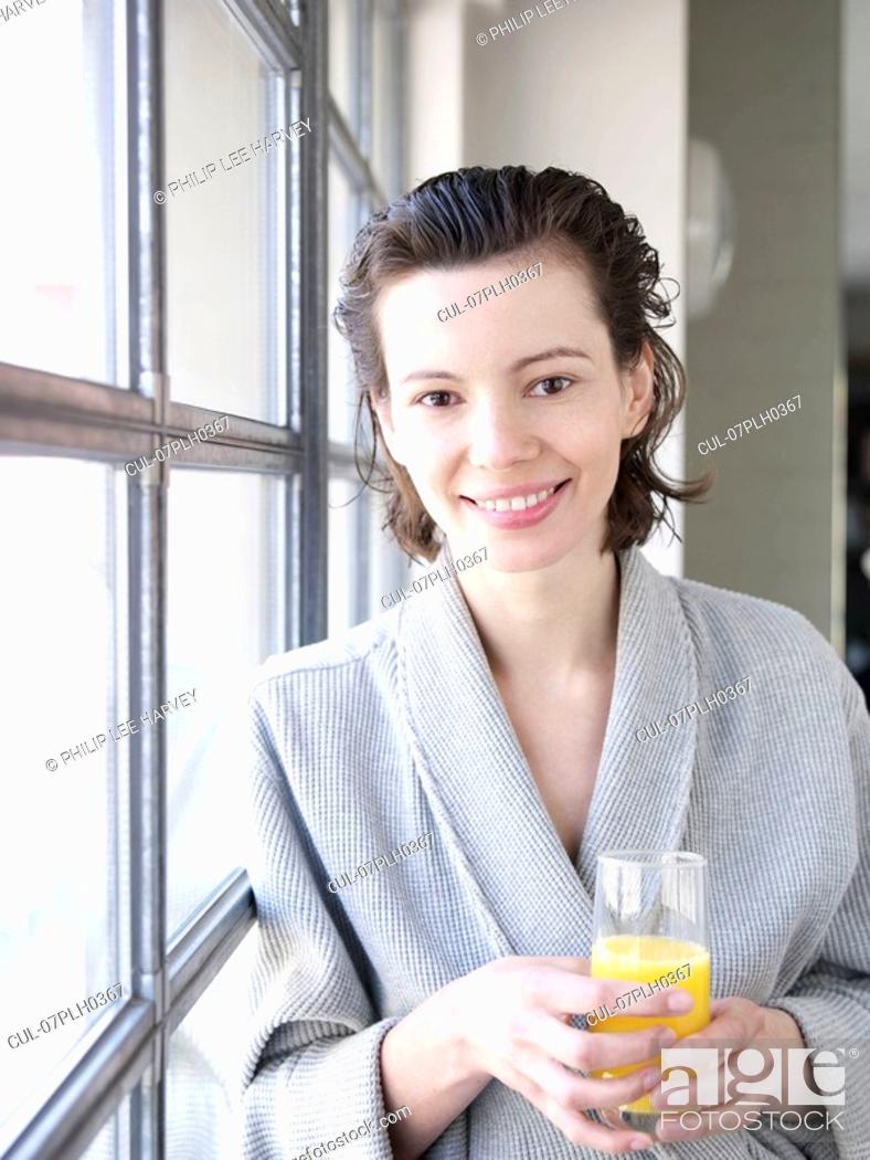 Stock Photo: Woman in bathrobe by window drinking.
