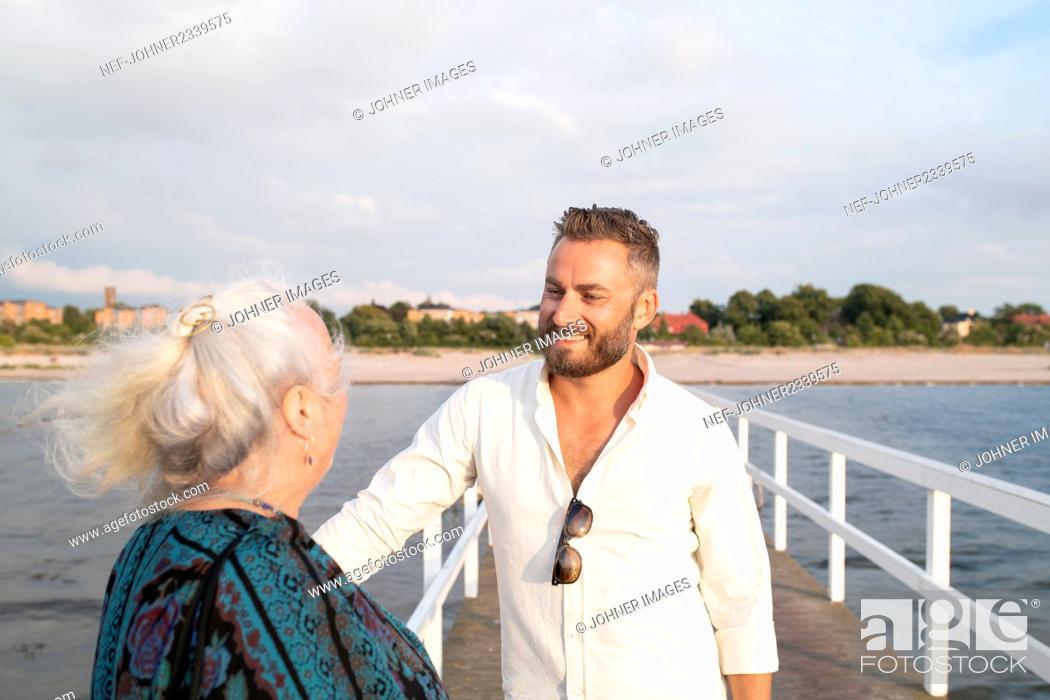 Imagen: Man with senior mother at seaside.