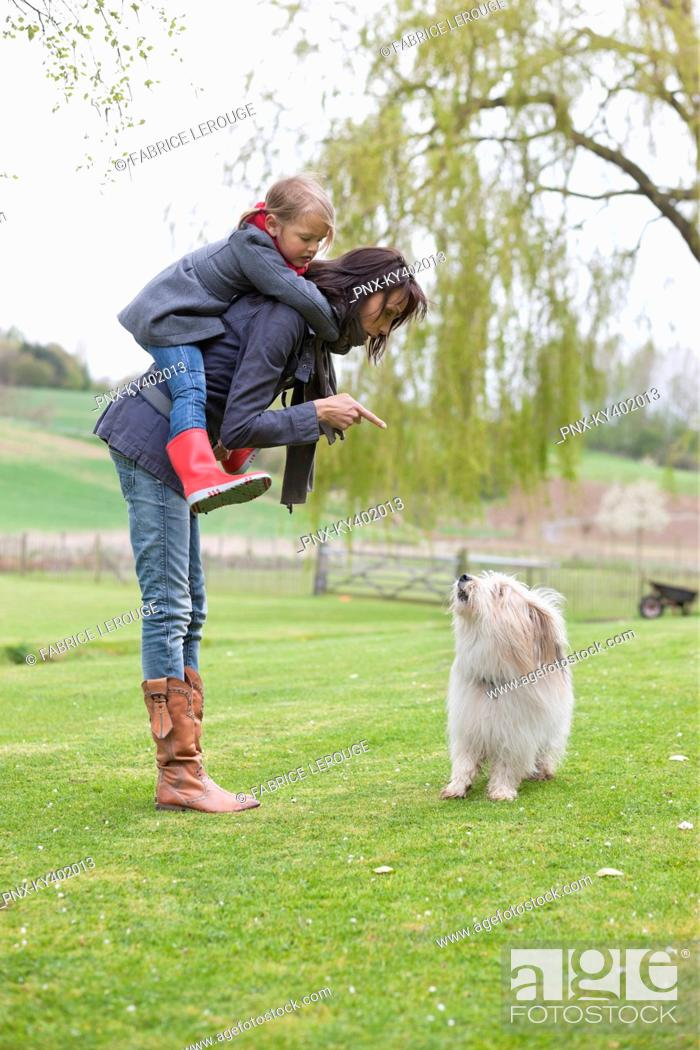 Stock Photo: Woman carrying her daughter on piggyback and scolding her dog.