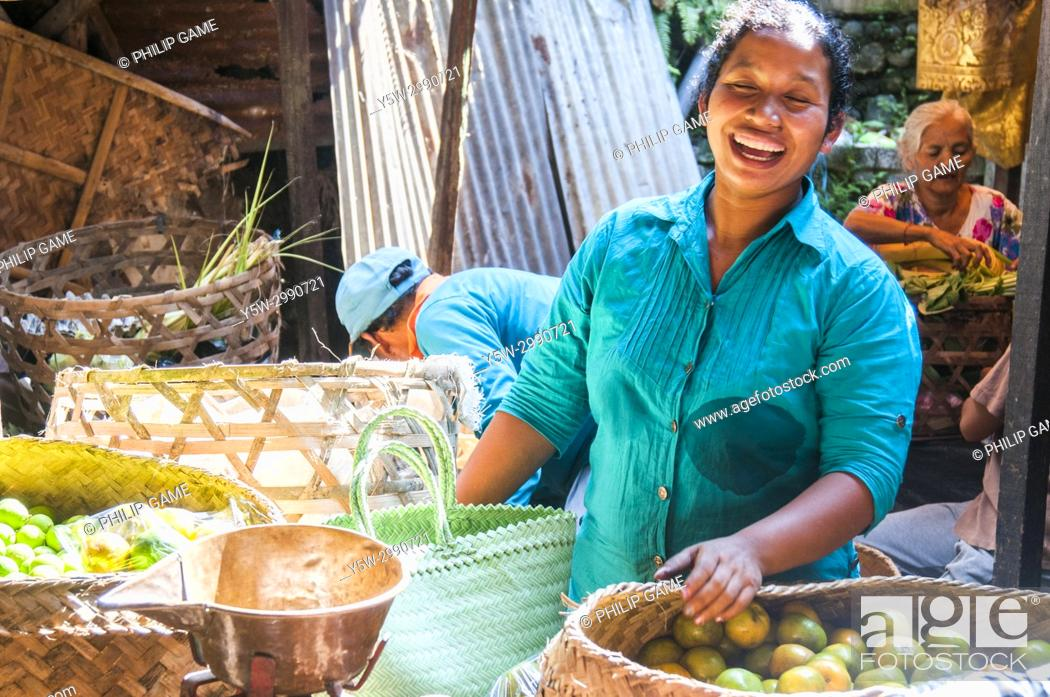 Stock Photo: Balinese woman laughing whilst she works in a produce market in Ubud, Bali, Indonesia.
