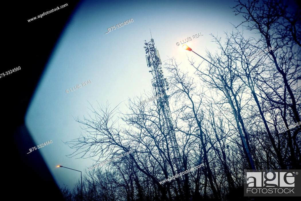 Stock Photo: Telecommunications tower around trees and lampposts view from a window at dawn. Bucharest, Romania, Europe.