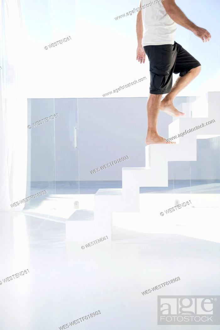Stock Photo: Spain, Mid adult man walking up stairway.
