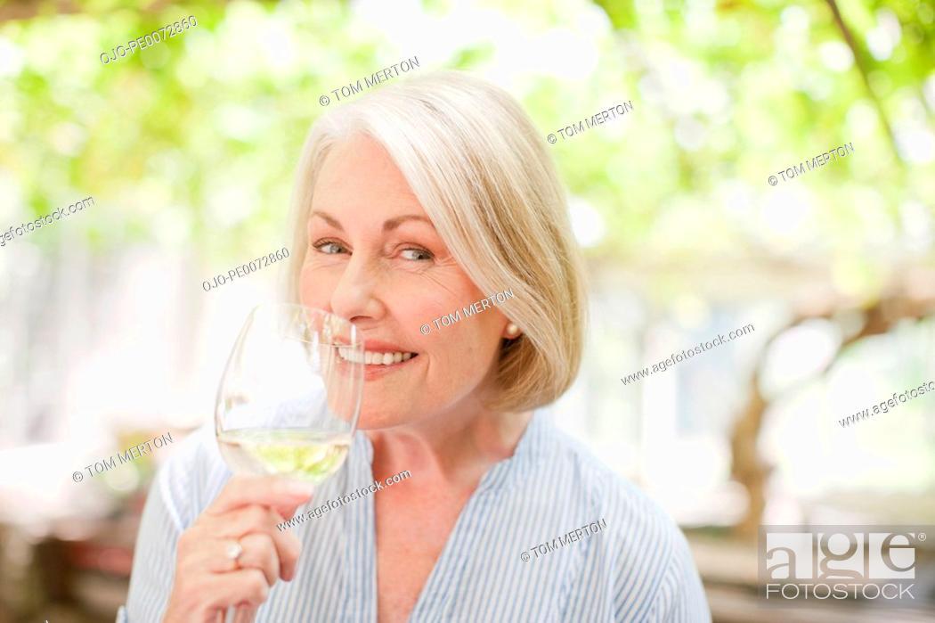 Stock Photo: Smiling woman drinking white wine.