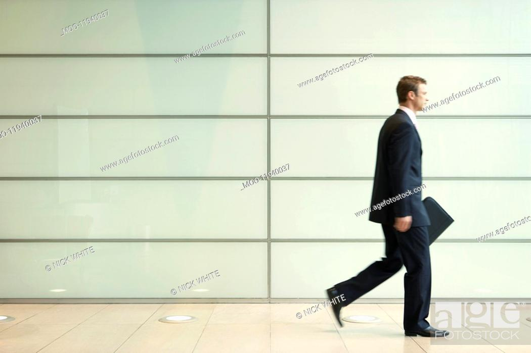 Stock Photo: Businessman Striding Down Office Corridor side view.