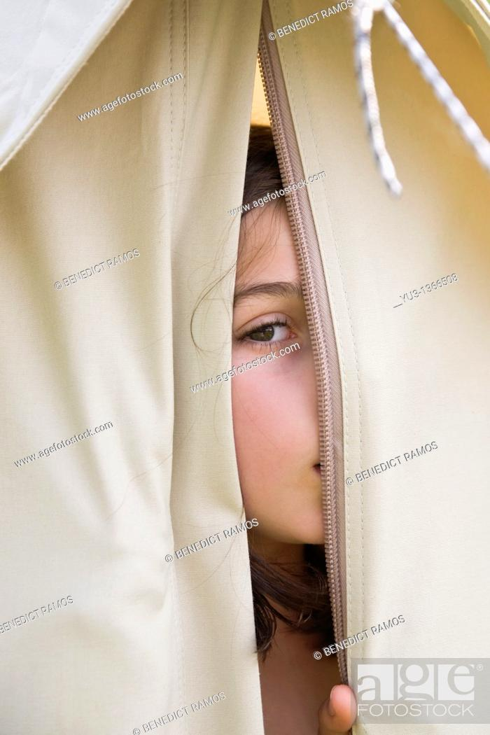Stock Photo: Young girl peeping through opening in a canvas tent.
