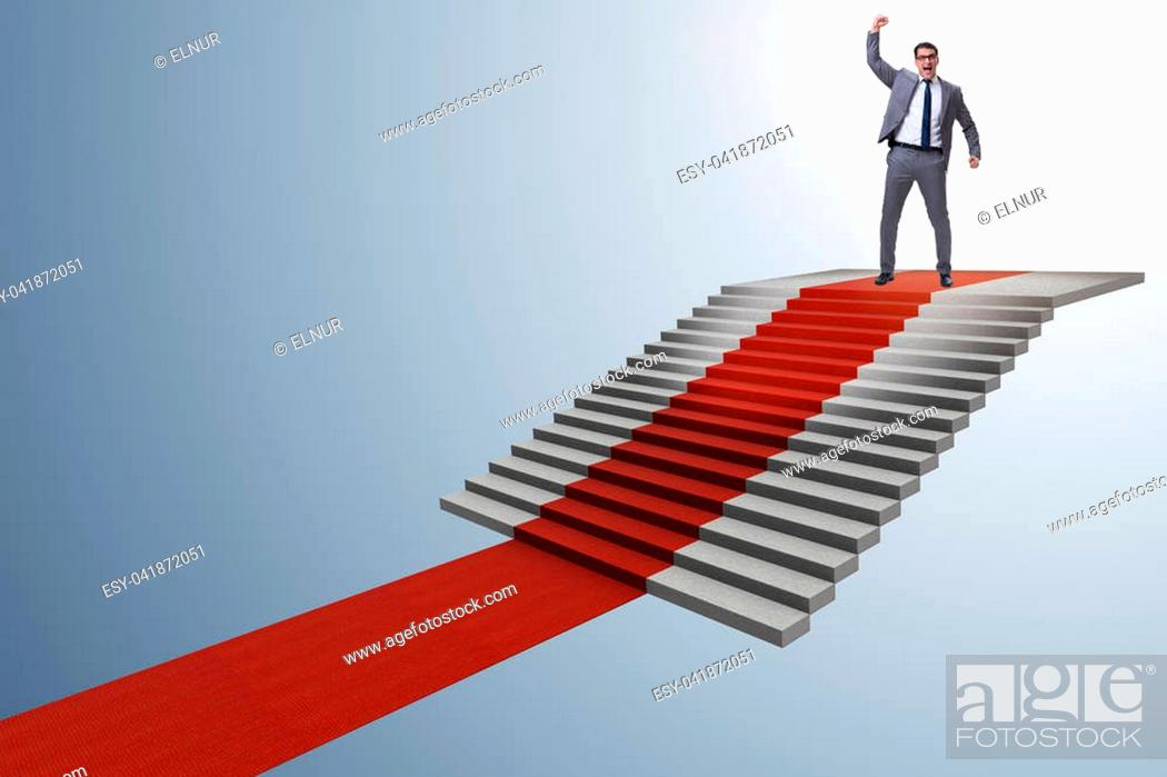 Stock Photo: Young businessman climbing stairs and red carpet.