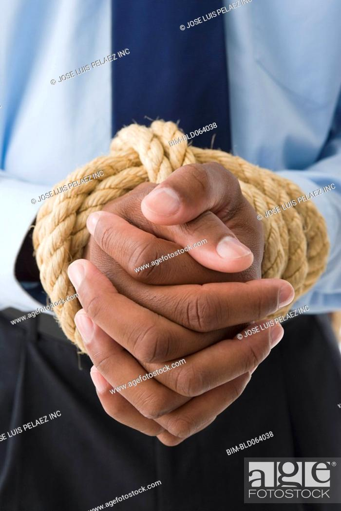 Stock Photo: Mixed race businessman with hands tied.