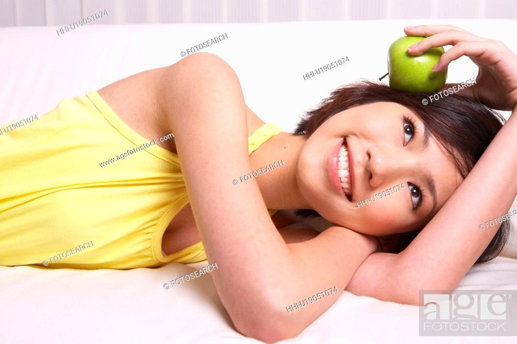 Stock Photo: Portrait of Natural Young girl holding Apple, Smiling.
