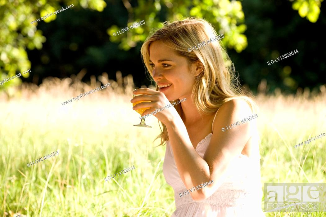Stock Photo: A young woman sitting on the grass, drinking a glass of orange juice.
