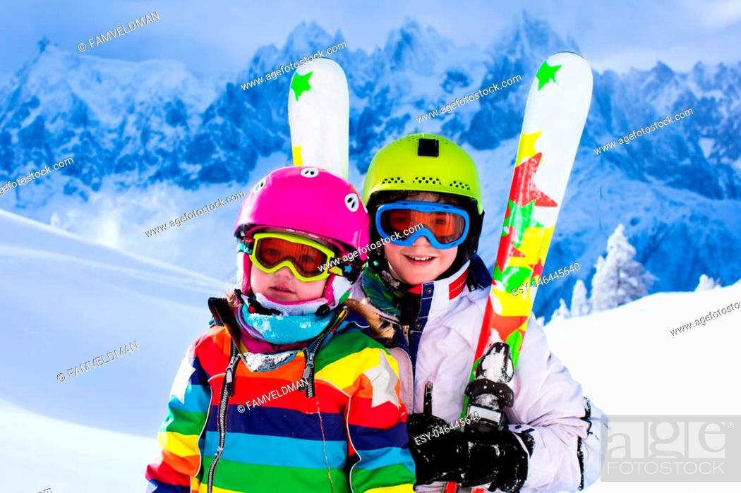 Imagen: Boy and girl skiing in mountains. Toddler kid and teenager with helmet, goggles, poles. Ski race for children. Winter sport for family.