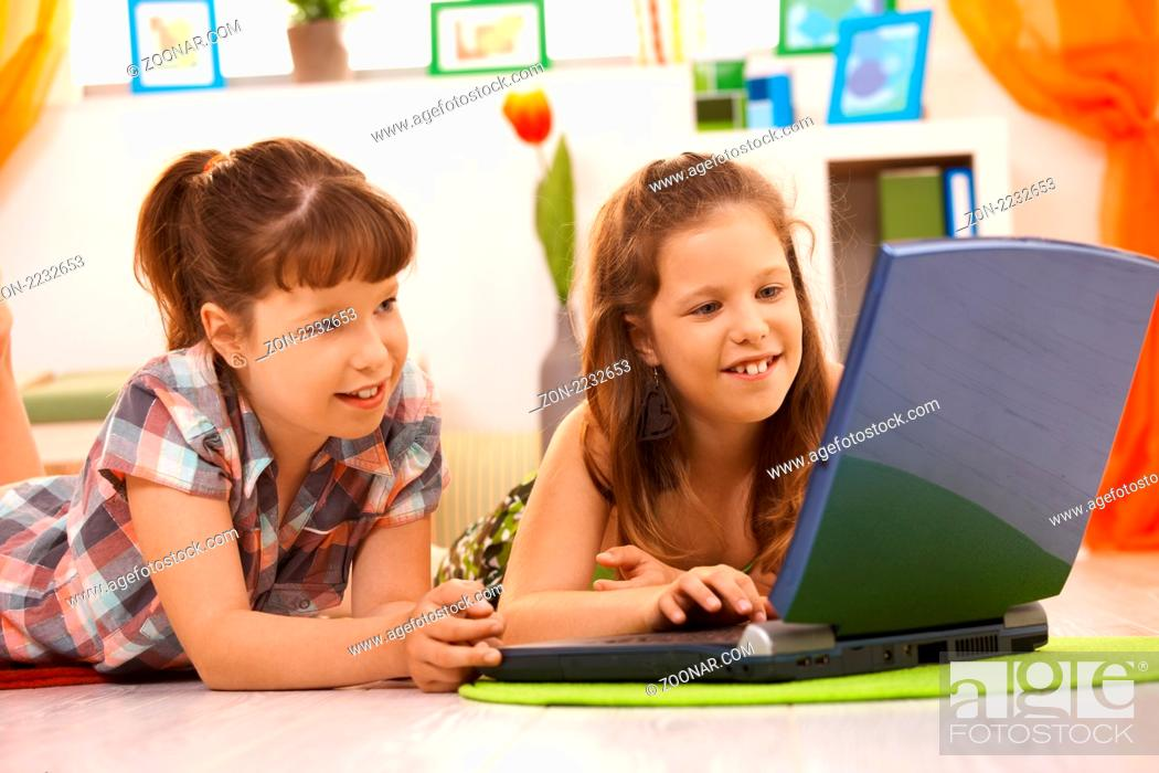 Stock Photo: Elementary age girls having fun together at home using laptop computer, browsing internet.