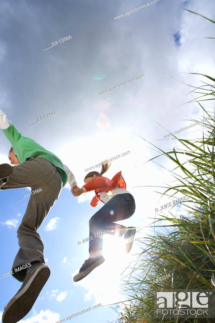 Stock Photo: Father and daughter 7-9 years jumping from grass outdoors, low angle view.