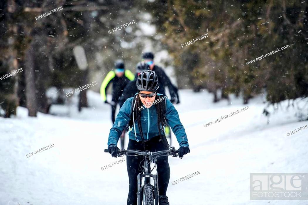 Imagen: A group of young mountain bikers riding on road outdoors in winter.